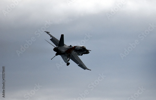 plakat Silhouette of F18 Hornet fighter aircraft in flight. Clouds in the background.