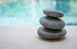 Natural Zen stone stack over blurred blue swimming pool background, outdoor day light, selective focus