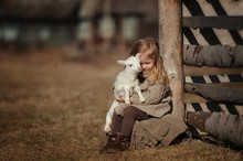 Little Girl With Lamb On The Farm. She Sits By The Fence And Hugs The Lamb.