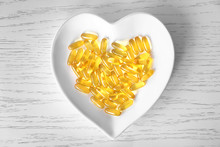 Heart-shape Plate With Fish Oil Capsules On Wooden Background