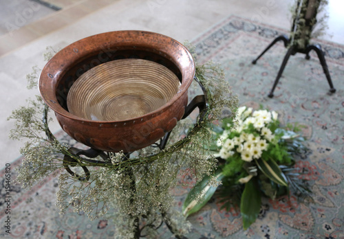 Small baptismal font in copper decorated with flowers during the Canvas Print