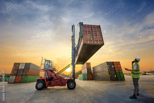 Fotografie, Obraz  forklift handling container in yard with foreman in charge under control