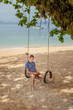 The man is sitting on a swing and reading an e-book. Lifestyle concept. Thailand, Krabi. February 2017.