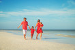 family with two kids having fun on beach