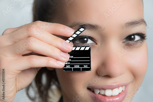 Photo  Smiling pretty teen woman and movie clapper