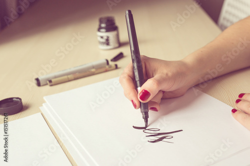 Fotografía  Hands writing with brush and ink, lettering