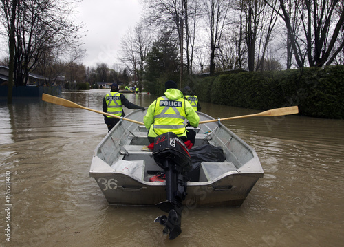 Police officers use a row boat on flooded the streets of St