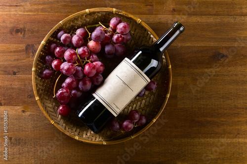 butelka-wina-lezaca-w-koszu-z-winogronem-widok-z-gory