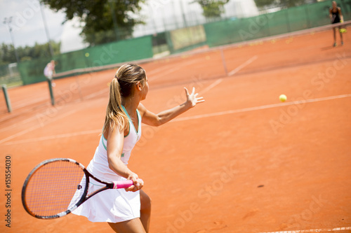 Pretty female tennis player playing on court on a sunny day
