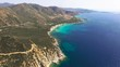 Drone fly over sardinia coastline and colorful turquoise mediterranean sea surraunded by high cliff and ancient ruins of a watchtower