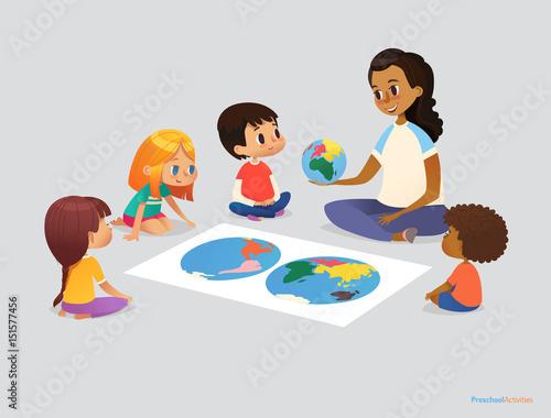 Zdjęcie XXL Szczęśliwe dzieci w szkole i nauczyciel siedzą w kręgu wokół atlasu i omawiają pytania geograficzne podczas lekcji. Koncepcja działalności przedszkola. Ilustracja wektorowa na plakat, reklama, strony internetowej, baner.