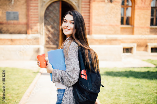 American university student smiling with coffee and book bag on campus Canvas-taulu