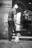 Starszy mężczyzna z psem na smyczy stoi przy wejściu do pasażu handlowego - 151586099