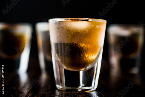 Spoed Foto op Canvas Bar Whiskey Shots with ice on dark wooden surface.