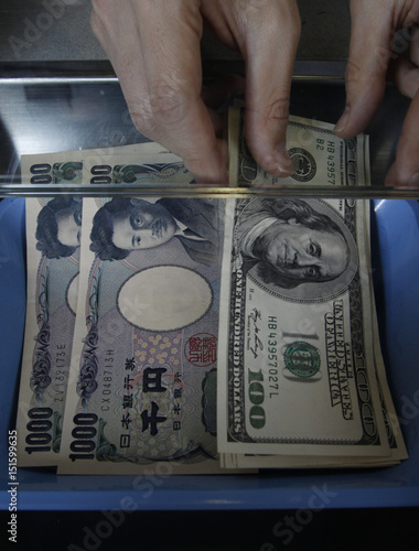 Money Changer Places Some One Hundred U S Dollar Bills Next To Anese Yens At An Exchange Booth In Tokyo