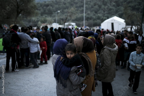 Refugees and migrants line up for a food distribution at the Moria
