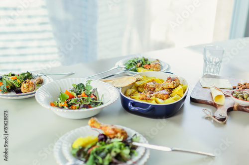 Photo  Roasted chicken with potato, green salads on table against window in modern apar