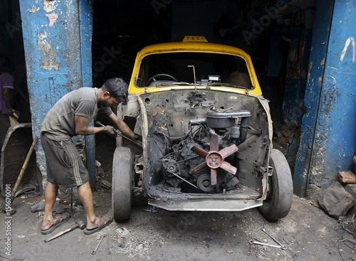 A Worker Dismantles An Ambassador Car Inside A Second Hand