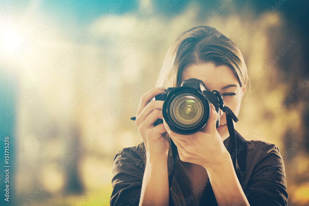 Fototapety, obrazy: Portrait of a photographer covering her face with camera.