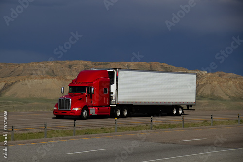 A red Peterbilt Semi Tractor pulls a white trailer down