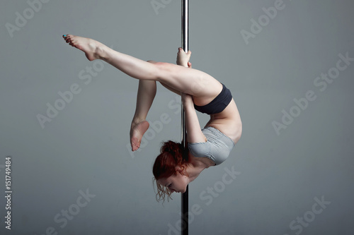 Fotografie, Obraz  Young woman exercise pole dance gray background