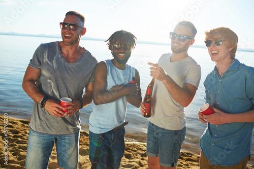Fotomural  Joyful guys in sunglasess spending day on the beach