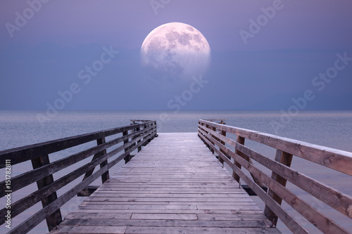 Full moon and viewpoint platform at sea dusk