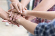 young college student joining hand, business team touching hands together - unity, harmony, teamwork, friends concept