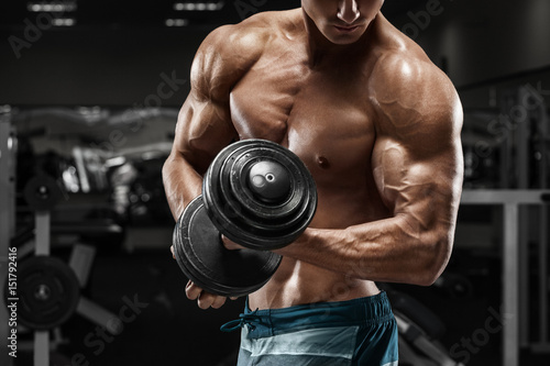 Muscular man working out in gym doing exercises with dumbbells, strong male nake Fototapeta