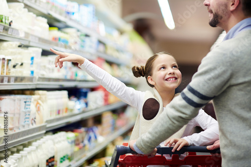Happy family buying groceries: smiling little girl choosing dairy products from Wallpaper Mural