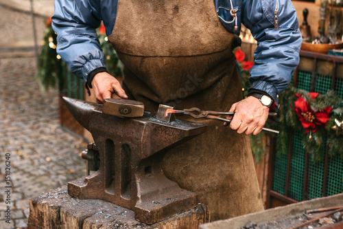 Blacksmith working metal with a hammer on the anvil in the forge