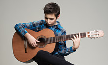 Caucasian  Boy Playing On Acoustic Guitar.