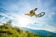 Professional Rider Is Jumping On The Bicycle, With Background Of Blue Sky. Sunny Summer Day.