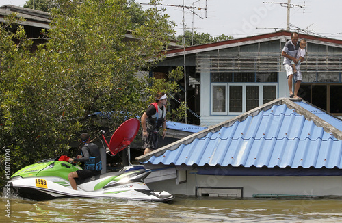 A man holds a child on roof of a submerged house as the