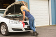 Blonde haired woman in jeans working on a car