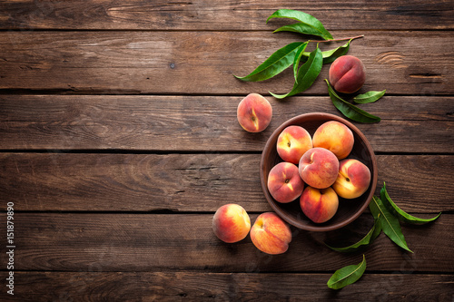 Fresh juicy peaches with leaves on dark wooden rustic background