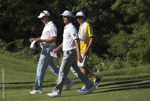 Ames of Canada walks with his son and caddy Ryan behind Weir of