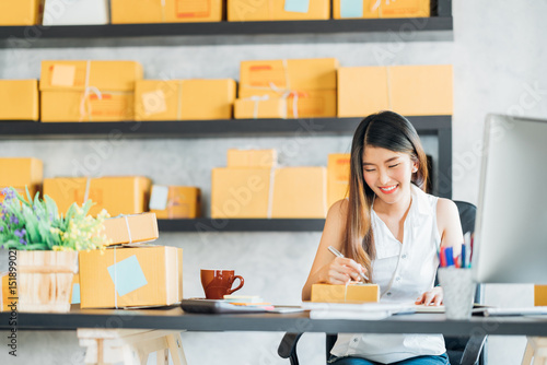 Fényképezés  Young Asian small business owner working at home office, taking note on purchase orders