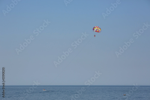 Spoed Fotobehang Luchtsport Two people flying on paraglider over the sea against clean blue sky background.