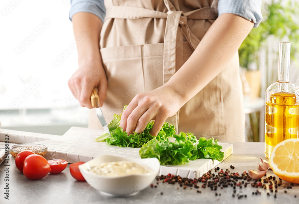 Fototapety, obrazy: Woman cutting lettuce on kitchen table