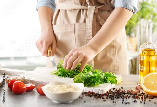 Fototapeta Woman cutting lettuce on kitchen table obraz