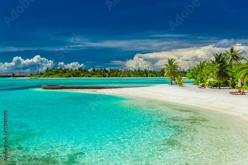 Staande foto Eiland Palm trees and beach umbrelllas over lagoon and sandy beach, Maldives island
