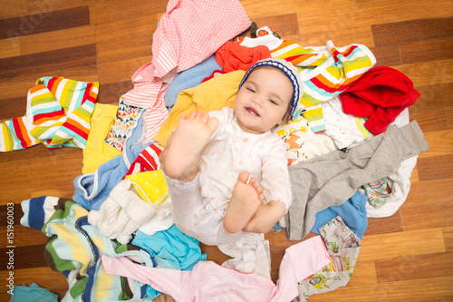 Happy baby girl on background with clothing Canvas Print