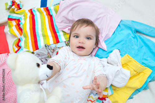 Photo  Happy baby girl on background with clothing and toy bear