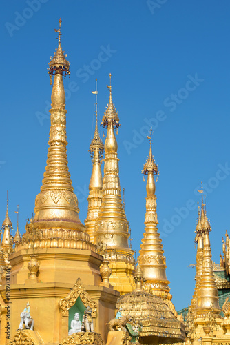 Foto  The tops of the golden stupas of the Shwedagon pagoda against the blue sky