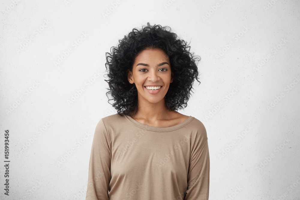Fototapety, obrazy: Waist up portrait of cheerful young mixed race female with curly hair posing in studio with happy smile. Dark-skinned woman dressed casually smiling joyfully, showing her white straight teeth
