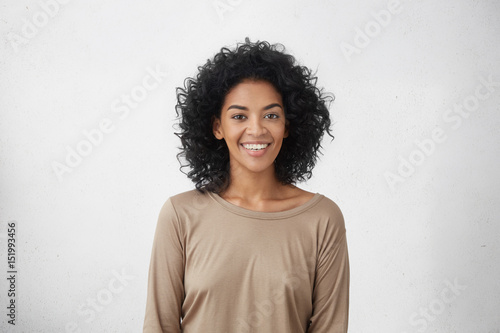 Waist up portrait of cheerful young mixed race female with curly hair posing in studio with happy smile. Dark-skinned woman dressed casually smiling joyfully, showing her white straight teeth