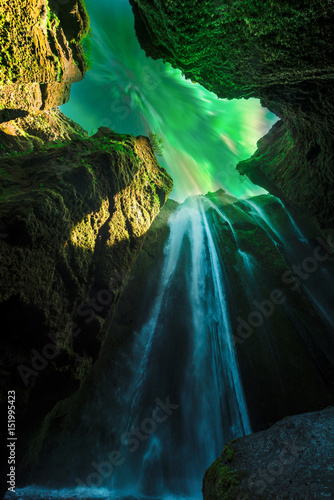 Photo  Green aurora light behind unique Gljufrabui waterfall