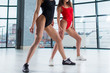 Close-up image of two young athletic female bodies and legs in swimsuits and trainers posing indoors