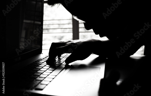 Fototapety, obrazy: silhouette black and white of anonymous hacker typing on keyboard of laptop for remotely hacking and receiving